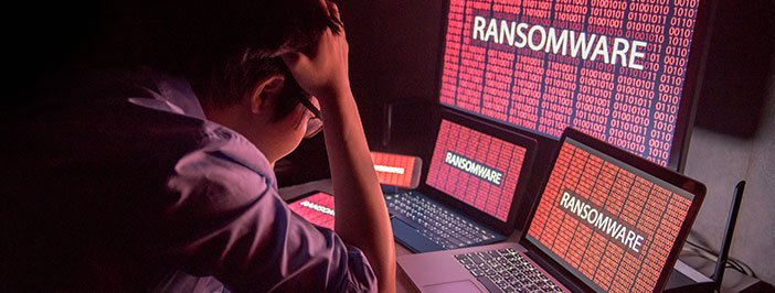 man in front of computer with ransomware attack on the screen